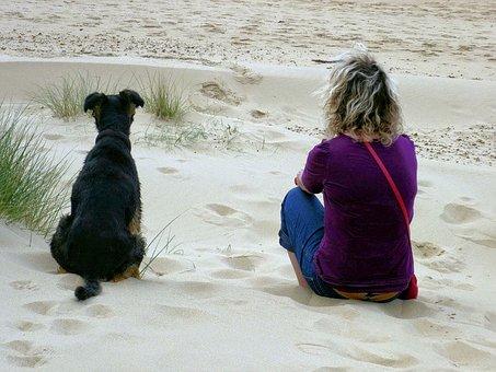 Lady and dog sitting on beach enjoying view